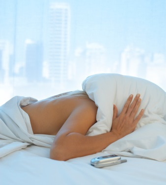 Woman lying in bed with pillow over head, city in background